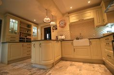 Cream shaker style kitchen designed by Amelia Wilson Interiors Ltd with stone effect floor tiles, cream herringbone metro wall tiles and copper accessories