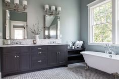 Stunning bathroom with basketweave marble tiled floors alongside a charcoal gray vanity with inset cabinet doors accented with nickel pulls and white marble counter with a marble mosaic tiled backsplash below a pair of rectangular pivot mirrors lit by polished nickel triple sconces with white shades.