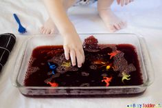 A Jello Dig is a sticky and delicious toddler activity. Toddlers find hidden objects in a bowl full of Jello in this fun sensory filled activity.