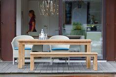Holztisch, Holzbank und bequeme Sessel: ein schlichtes Outdoor-Esszimmer für die Terrasse