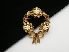 Lovely gold tone plated Avon brooch featuring an antiqued gold tone mounting in a wreath design. The beautiful wreath is set with simulated pearls and red ruby rhinestones.