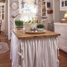 Turn an old table into a cottage-style kitchen island by adding a cloth skirt and storage underneath.