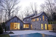 "This weekend house was designed with local stone and wood to maximize the expression of a typical country ""cottage."" The owners required a modern residence that would blend in with the character of its Connecticut wooded area context. Modern Barn House, Haus Am See, Parasols, Weekend House, Modern Farmhouse Exterior, Farmhouse Windows, Farmhouse Style, Style At Home, Stone Houses"