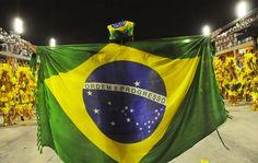 Bandeira do Brasil serve de capa no meio da avenida durante desfile da Beija-Flor.