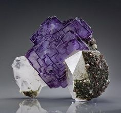 Fluorite from Yaogangxian Mine, Hunan Province, China. The freestanding fluorite cluster is complete all around the top, sides, and the back, only contacted on a tiny portion of the bottom/rear of the specimen. It is translucent, and pristine on all the faces. The sharp steppes are highlighted by a thin, intense purple phantom.