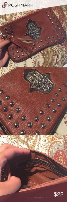 Beautiful Studded Hamsa Clutch Brand New Brand New. Never used. Vegan brown Leather.. Sweet little tassle clipped on the end. Small pocket compartment inside. Fill this beauty with make up, money, your Id, your phone and show it off!! Super convenient and adorable. Bags Clutches & Wristlets