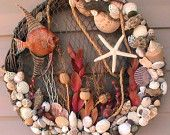 Large wall art wreath using an orange angel fish, starfish and a variety of shells.  Netting in background with rope accenting.