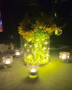 I saw this centerpiece at a graduation dinner in LA. It would be easy to duplicate. Arrange sunflowers in a mason jar, and wrap fairy lights around the inside of a larger glass container. Place the mason jar with sunflowers inside the larger container. Complete the look with glass votives. Beautiful!