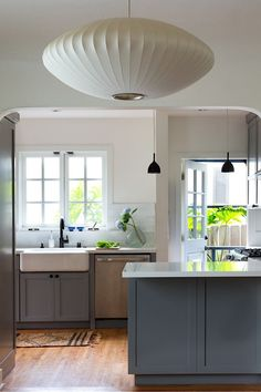 Project M Kitchen | Remodelista.  Nelson saucer pendant and grey cabinets, farmhouse sink, black hardware
