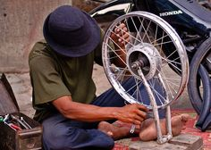 Man fixing motorbike wheel outside Wat Moha Montrei.