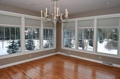 Plenty of windows let in natural light in this sunroom with grey walls and wood floors. Blinds give the room the chance for privacy and a chandelier adds elegance.