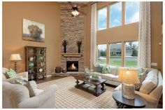 A two-story wall of windows and a stunning stone fireplace are distinctive features of the Drake plan. By Ryland Homes at Post Preserve. Cumming, GA.