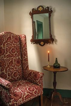 In the dining room sits a tall wing chair in reproduction fabric.