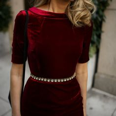 Mary Orton of Memorandum wears a Boden red velvet sheath dress, a black embellished waist belt and a black YSL cross body bag for an office holiday cocktail party