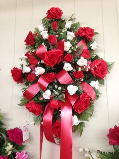 Silk funeral spray using red roses, red and white rosebuds and white filler with red ribbons.  October 2015