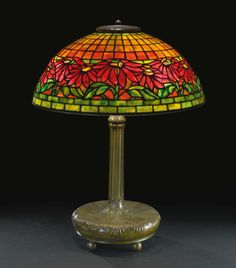 "Tiffany Studios ""POINSETTIA"" TABLE LAMP shade impressed TIFFANY STUDIOS NEW YORK 1558 base impressed TIFFANY STUDIOS/NEW YORK/25783 with the Tiffany Glass & Decorating Company monogram leaded glass and patinated bronze 23 in. (58.4 cm) high 17 7/8  in. (45.4 cm) diameter of shade circa 1910"