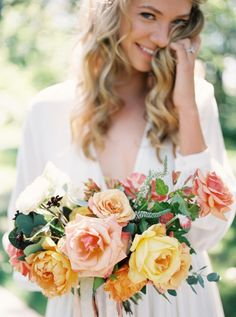 wedding bouquet with garden roses in peach, yellow, orange and red for late…