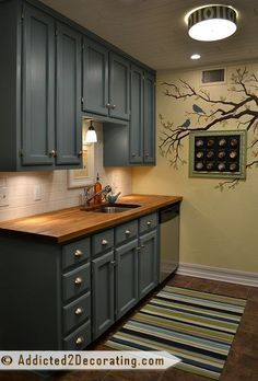 small condo kitchen with teal cabinets, white subway tile backsplash, and oak butcherblock countertops