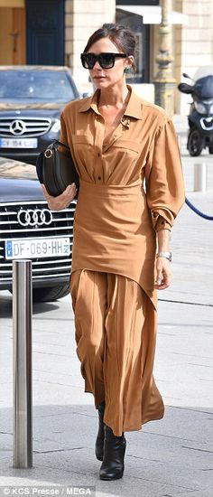 Fashionable arrival: The Spice Girl looked typically chic in one of her own designs as she...