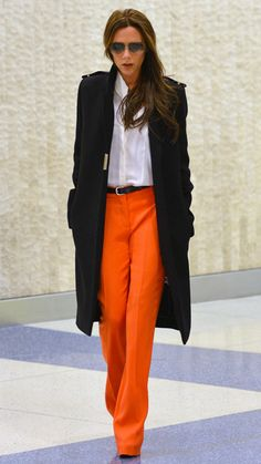 Victoria Beckham wears a black coat, white dress shirt, orange wide trousers and black leather belt - Buy the + Look +: + https: //lookastic.de/damenmode/wie-kombinieren/mantel-businesshemd-weit-hose-g - Moda Victoria Beckham, Victoria Beckham Outfits, Victoria Beckham Style, Victoria Beckham Fashion, Victoria Beckham Clothing, Fashion Mode, Work Fashion, Trendy Fashion, Fashion Outfits