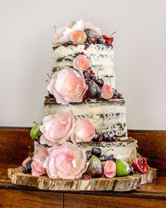 Naked wedding cake with edible lace, rice paper flowers and figs, cherries, blueberries and pomegranates.