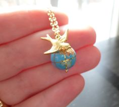 World globe necklace - small gemstone Earth bead and traveling brass bird on delicate gold plated chain - You're Not So Far Away. $25.50, via Etsy.