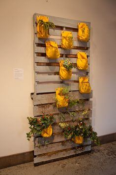 Idea from the May Flea Off Market. 2 Pallets painted, stacked on top of each other, and fastened to a wall. Bags are fastened to the pallets for plants.        The bottom of the stack is filled with dirt, etc as well.       Easy to do and looks really cool. yard-garden-diy