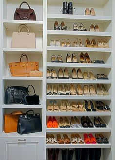 Chic Walk In Closet Features Floor To Ceiling Sloped Shoe Shelves Situated  Next To A Buil Tin Shelving Unit Dedicated To Designer Purses.