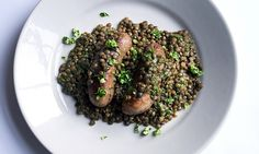 Two sausages on a bed of lentils with specs of green rocket