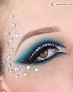 Pretty teal and silver eye shadow with stylized black eye liner and crystal enhancements.