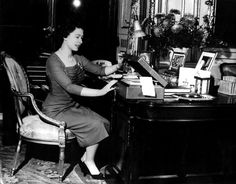 1959: The Queen works at her desk in Buckingham Palace, opening one of the 'boxes' in which documents and papers, sorted for her attention, are sent by her Private Secretary
