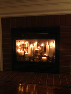 """Replaced cheap, builder vent free gas logs that didn't work well and vented into house with """"candle fireplace"""". Pete made base out of plywood for me and I painted it black. Had Lowes cut me three pieces of mirror glass to line the back of the firebox and then I antiqued the mirrors so they weren't so shiny, but still reflected the candle light."""