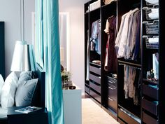walk-in closet formed using a curtain behind the bed