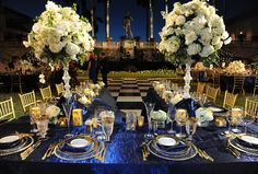 This real-life reception was worthy of royalty with luxe navy linens, gold dinnerware and dramatic centerpieces! // Photo courtesy of Damon Tucci.
