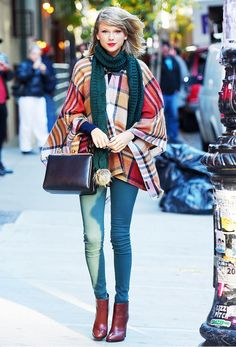 Taylor Swift wears a teal scarf, a plaid poncho, skinny jeans, red leather boots, and a top-handle bag