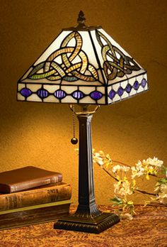 "Trinity Knot Lamp:  Reminiscent of highly prized Tiffany lamps of the late 19th century, this is a classic with a Celtic twist. Leaded glass knots in vivid shades of blue and deep violet glow against a background of luminous ivory-tone glass, all atop a decorative bronze-finished metal base. Ideal size for foyer, desk or bedside, lamp measures 18"" in height."