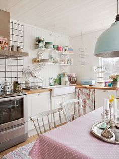 Vintage Kitchen: Open shelves lovingly display a vintage collection, a charming farmhouse sink, and silver candlesticks tie together a beautiful and eclectic room.