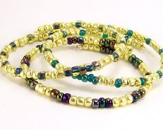 This is a set of 3 memory wire stacking beaded bracelets.. I used larger sized glass seed beads, the gold have a slight nugget shape. Color comes from three different bead types each bracelet is different.. All color beads are shades of blues and greens.. All three accent each other..  Ware 1, 2, or all 3 bracelets.. Or, mix and match with other bracelets..Made and Ready to Ship...Bracelets will fit average wrists very comfortably with room to spare..Memory wire has a slight oval shape and…