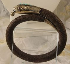 Victorian Snake bracelet with ornate chase work on head and tail. Head is accented with natural turquoise; eyes are set w/garnets. Flexible bracelet is comprised of woven brown hair and gold head tail. Snake Bracelet, Snake Jewelry, Hair Jewelry, Victorian Jewelry, Antique Jewelry, Locket Design, Victorian Hairstyles, Mourning Jewelry, Memento Mori