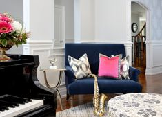 A bright living room with a gorgeous color palette of gray, gold, fuchsia, and midnight blue. Subtle patterns on the ottoman, area rug, and throw pillows complement the vibrant colors while not taking attention away from the artwork. Home located in Vaughan, Ontario. Designed by Lumar Interiors who also serve Richmond Hill, Aurora, Nobleton, Newmarket, King City, Markham, Thornhill, York Region, and the Greater Toronto Area.