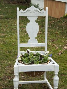 My upcycled chair. Took an old chair, took the seat out, used some leftover paint, only 1 coat for that disstressed look, then used a planter made with recycled material and planted some beautiful flowers. Put planter in seat hole, and voila! Beautiful planter!