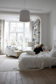 Bedroom with a large window, a double bed, sofa and storage shelving, and a rug on the floor