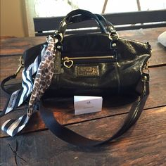PRICE REDUCTION! Coach purse 1941 Coach Black Daisy Liquid Gloss Purse.  Perfect condition.  Carried one time.  Has detachable shoulder strap, care instructions, bow, and Coach tags.  Black lining with a zipper pocket inside and two open pockets inside.  One zipper pocket on the outside with gold heart.  No trades please.  13 1/2 L, 11 1/2 H, 5 1/2 W. Coach Bags Shoulder Bags