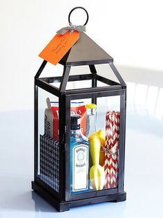 Great summer hostess gift - fill a lantern (IKEA has good, cheap ones) with booze, cute napkins/straws, citrus reamer, mixer, lemon, and bar snack. Gift basket Ideas #giftbasketideas #giftbaskets