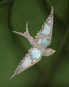 An antique opal and diamond swallow brooch, circa 1870 pavé-set with diamonds, centering free-form opals, enhanced by ruby cabochon eyes; retailed by Garrard, with signed box; estimated total diamond weight: 4.25 carats; mounted in silver-topped fourteen karat gold; length: 4in. (pin stem is detachable).  Accompanied by Garrard appraisal, dated January 16, 1981.