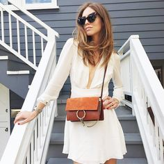 Chiara Ferragni of The Blonde Salad wearing a white long sleeve dress with a plunging neckline and a brown suede cross-body bag with chain detail