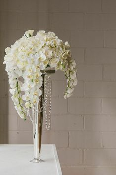 Modern and Glamorous Silk Flower Arrangement. Can you believe these flowers are silk?! Afloral.com has high-quality faux orchids, roses, peonies and hydrangeas that will fit any wedding budget.