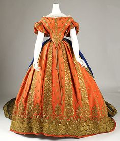 Haute Couture Victorian fashion court dress gown ensemble from Italian 1857-1860 19th century #Historical #Costume. Made from silk,  gold metallic embroidered flower floral, bead, sequin and lace trimming. Embroidery on decollete, flounced sleeve creates a decorative effect emphasizes the bodice,  waistline and hem. Full hips are enhanced by puffed skirt and petticoat. The back is in contrasting color where it emerges and flow into a graceful train. #Hautecouture #Vintage #Victorian #Fashion