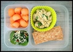 """Curry chicken salad, whole wheat """"ak-mak"""" brand crackers, cantaloupe, and a small spinach salad with cheese, toasted almonds and olive oil."""
