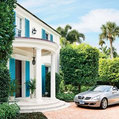 Just beyond an emerald wall of boxwoods on a quiet, palm-lined street, a whitewashed home with electric blue shutters rises like the sun peeking over the horizon line. Amid the glamour of Palm Beach, the 1940s house had persisted as glitzy estates and mod